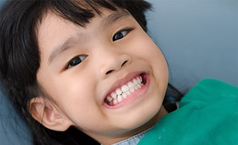 Child smiling after fluoride treatment