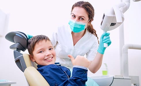 Child giving thumbs up after pulp therapy
