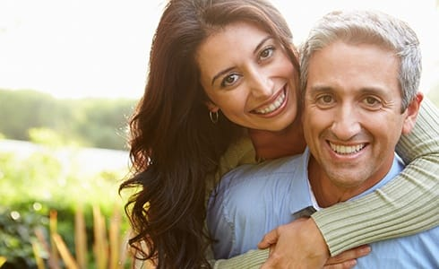 A middle-aged couple hugging and smiling while enjoying the outdoors after seeing their HealthChoice dentist in Oklahoma City