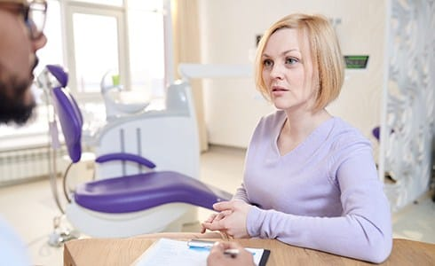 A young woman with short, blond hair speaking to her dentist about the need for a dental crown