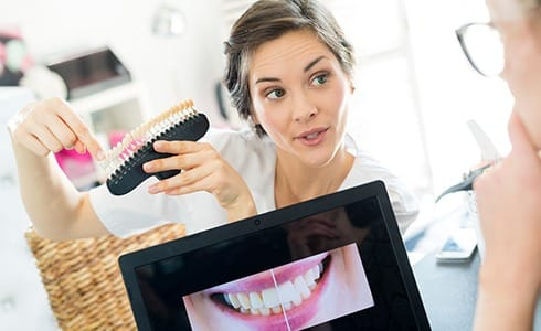 A dentist showing a patient what her smile will look like after receiving veneers and pointing to a shade guide to show her the new color